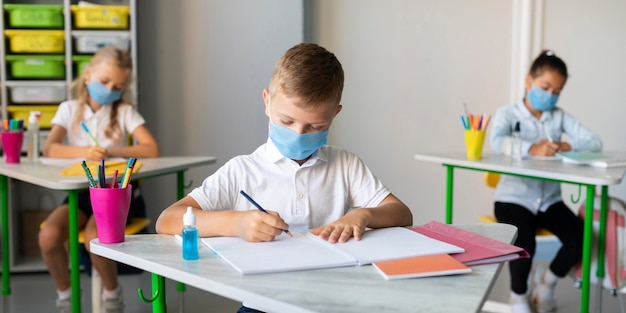 Kids writing in classroom while wearing medical masks