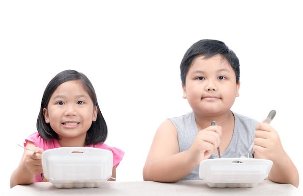 Kids едят жареный рис в коробке из пены изоляции