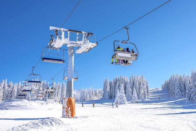 Kiers on a ski lift at a mountain resort with the sky and mountains