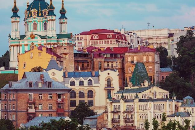 Г. киев. старый город. украина. прекрасный вид на старинную улицу андреевский спуск и андреевскую церковь среди зеленых деревьев замковой горы в киеве.