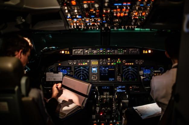Киев киев украина - декабрь 2019 пилоты авиалайнера за работой. вид на кабину. летные приборы и оборудование. кабина экипажа самолета. вид из кабины самолета на небоскребы и городские кварталы