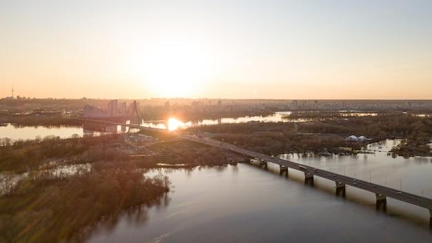 キエフウクライナのオボロン地区の美しい夕日を背景にしたキエフノースブリッジ。夕方の日差しの中で橋。ドローンからの写真