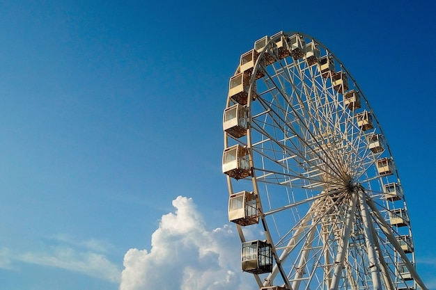 Колесо обозрения киев на фоне красивого ярко-голубого неба с пушистыми облаками на закате