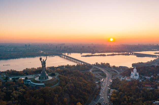 Skyline di kiev oltre il bellissimo tramonto infuocato, ucraina. patria del monumento.