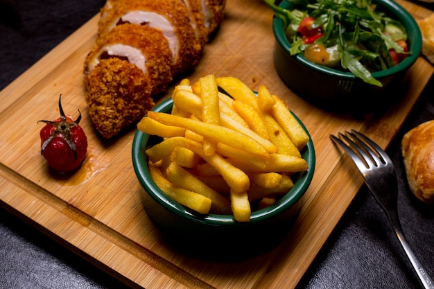 Kiev style cutlet on the wooden board with french fries arugula tomato cucumber sauce side view