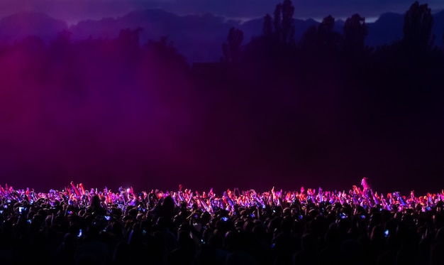Kiev, ukraine - jul 01, 2017: crowd of spectators at a concert at night lit by a spotlight from the stage against a background of nature and dramatic storm clouds