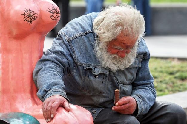 키예프, 우크라이나 - 2009년 10월 3일: 슬픈 노숙자가 손에 초콜릿 바를 들고 벤치에 앉아 있습니다.