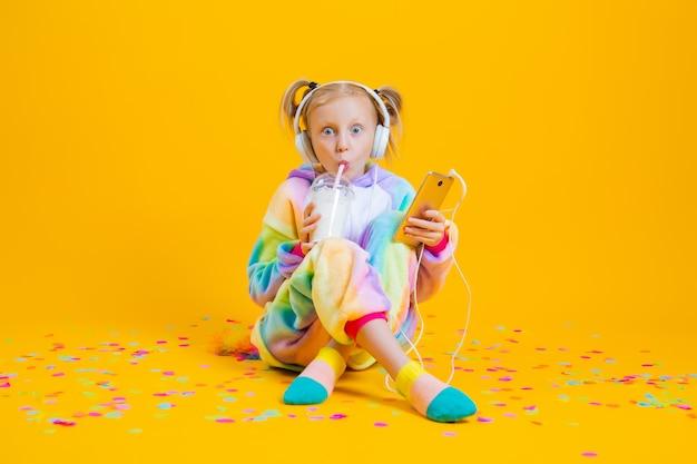 Счастливая маленькая девочка в единороге kigurumi слушает музыку в наушниках, держа смартфон