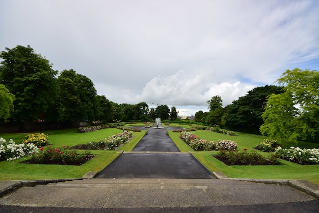 Kilkenny castle garden surrounded by greenery under a cloudy sky in ireland