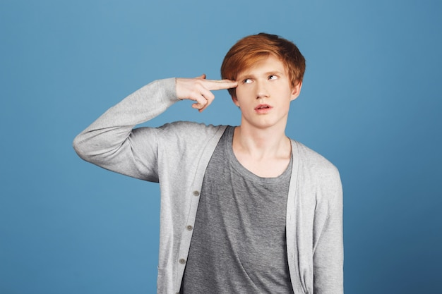 Kill me please. young good-looking tired male student with ginger hair in casual gray outfit making gun gesture with hand, showing he exhausted with deadlines in university.
