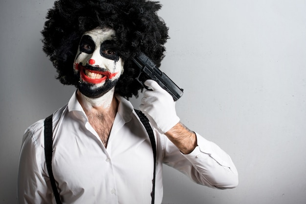 Killer clown cometing suicide on textured background