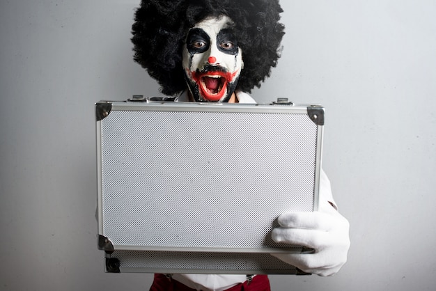 Killer clown holding a briefcase on textured background