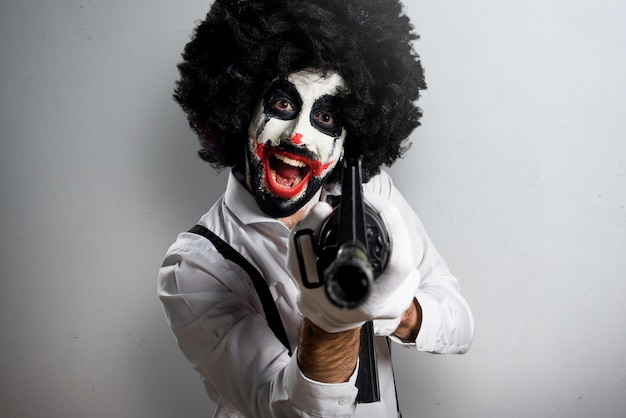 Killer clown holding a rifle on textured background