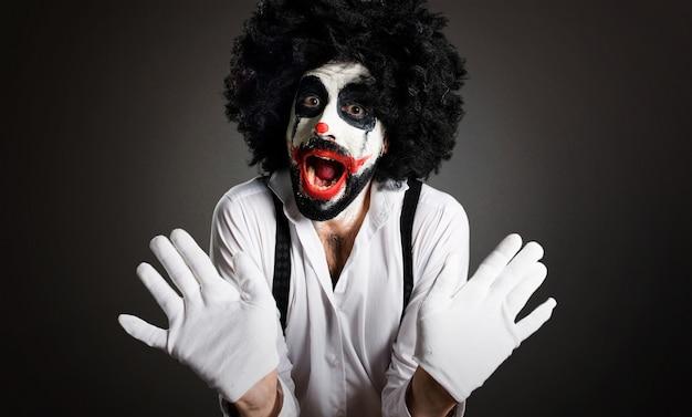 Killer clown making surprise gesture on textured background
