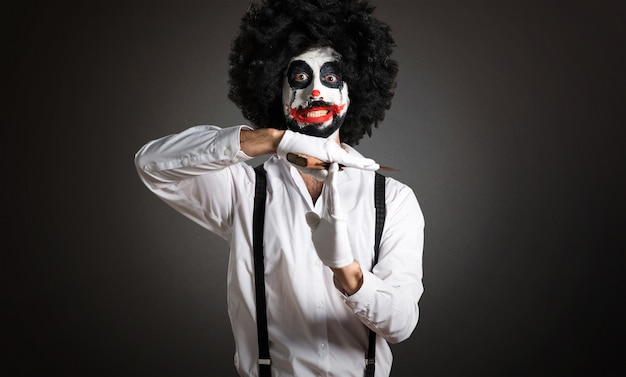 Killer clown making time out gesture on textured background