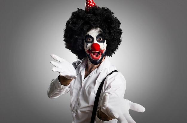 Killer clown presenting something on textured background