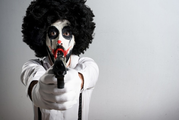 Killer clown shooting with a pistol on textured background