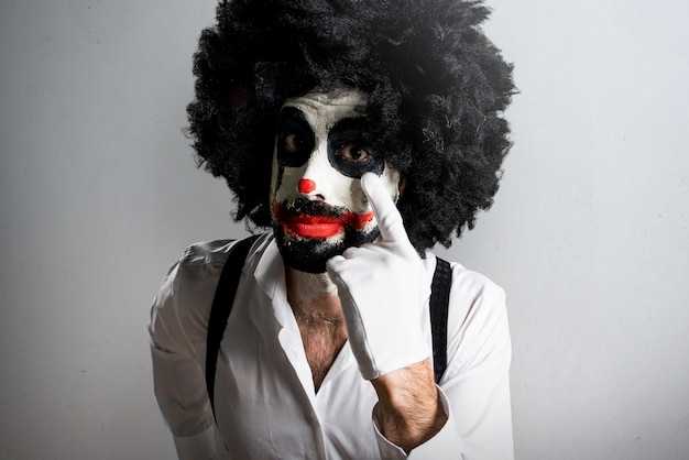 Killer clown showing something on textured background