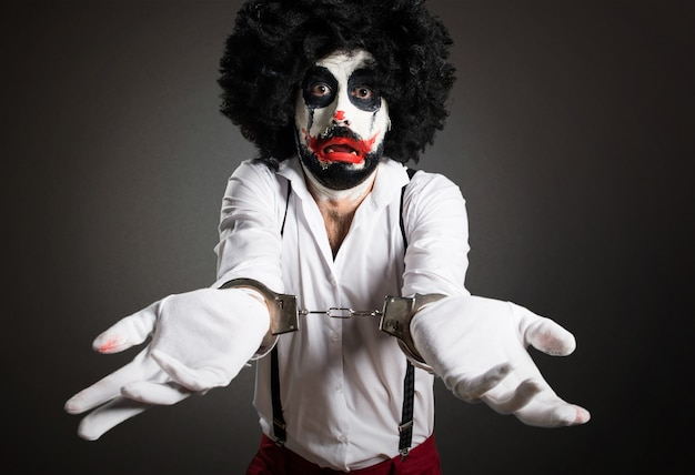 Killer clown with handcuffs on textured background