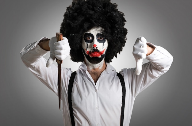 Killer clown with knife making bad signal on textured background