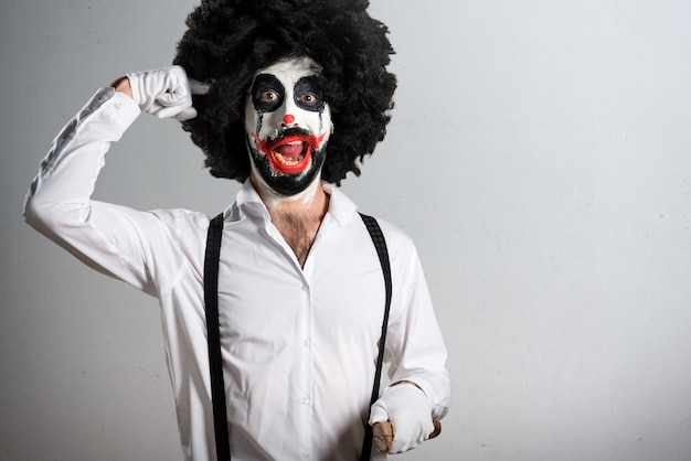 Killer clown with knife making crazy gesture on textured backgro