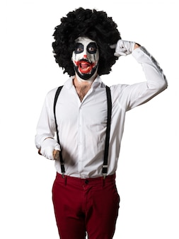 Killer clown with knife making crazy gesture