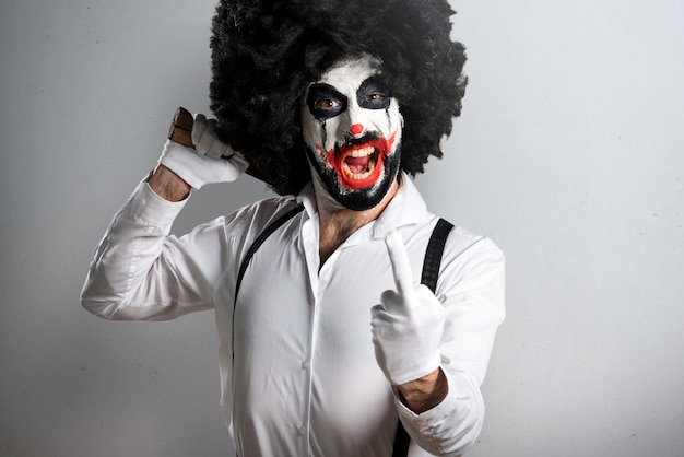 Killer clown with knife making horn gesture on textured backgrou