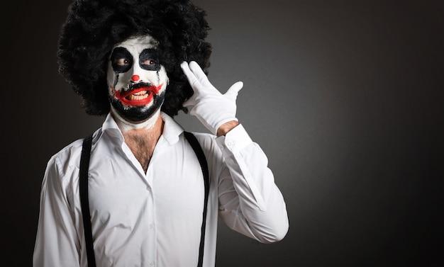 Killer clown with knife making suicide gesture on textured backg