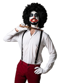 Killer clown with knife making suicide gesture