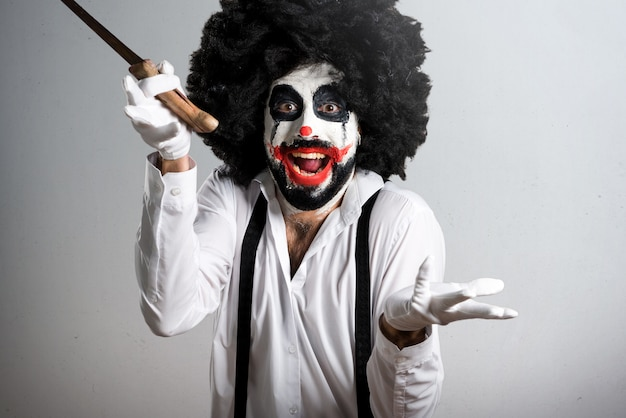 Killer clown with knife making surprise gesture on textured back