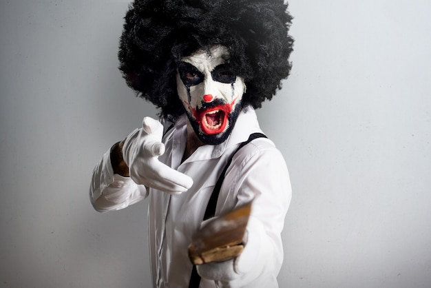 Killer clown with knife shouting on textured background