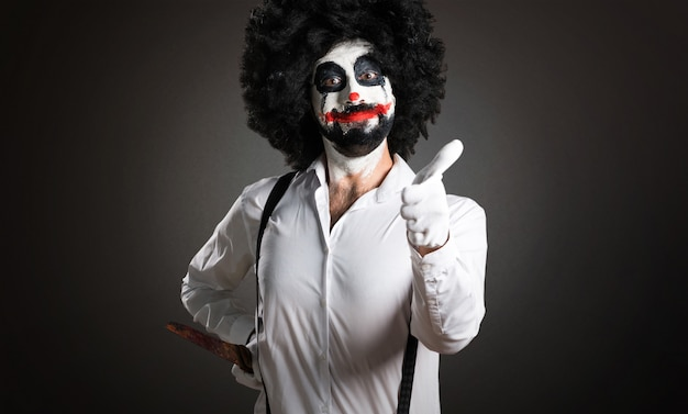 Killer clown with knife with thumb up on textured background