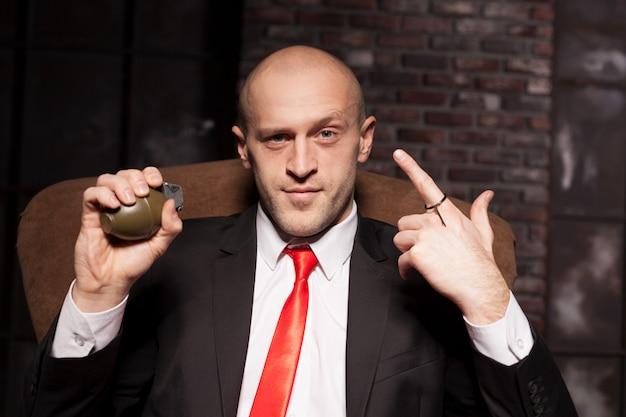 スーツとネクタイを着たキラーが手榴弾ピンを引く準備ができている