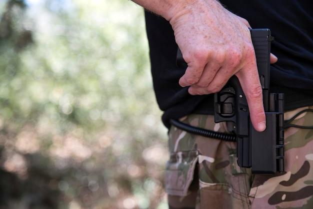 キラーまたは銃を持ったアメリカ人警官は、テキストの概念のためのコピースペースで緑の背景の上にクローズアップします。警官、ホルスター9mm拳銃で手持ちのクロップド。法と秩序。軍。兵士。軍隊。戦争