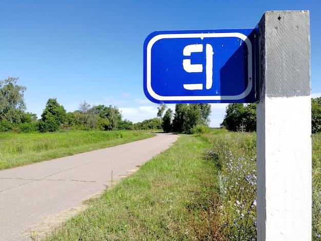 Километровый знак с цифрой 9 на столбе сельской дороги летом.
