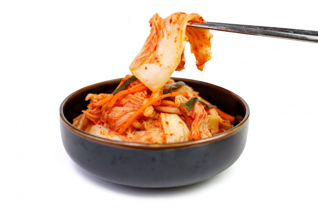 Kimchi cabbage in a bowl with chopsticks on white background, top view.
