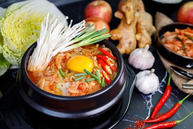 검은 배경에 김치 재료와 함께 그릇에 김치 양배추 수프