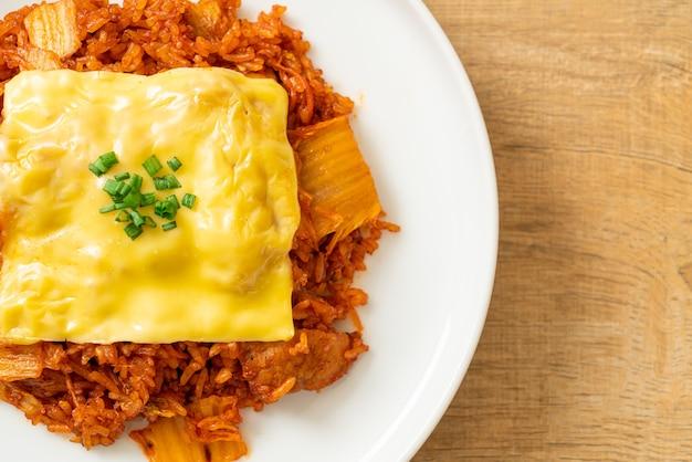 돼지 고기와 치즈를 얹은 김치 볶음밥. 아시아와 퓨전 음식 스타일