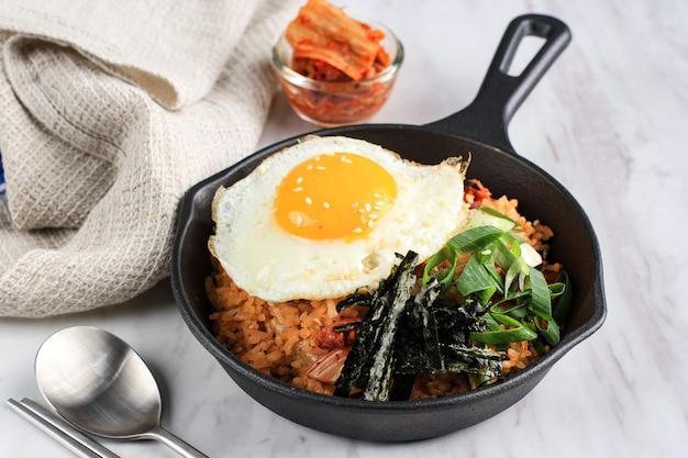 Жареный рис кимчи с водорослями, солнечным бокалом сверху и белым кунжутом - корейский стиль еды (кимчи боккеумбап)