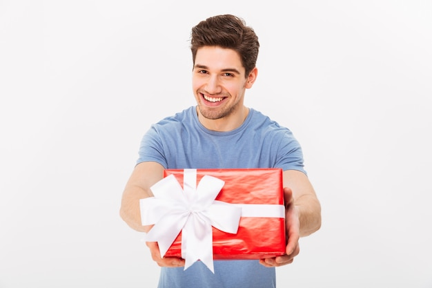 Kind attractive man with beautiful smile giving birthday present on camera, isolated over white wall