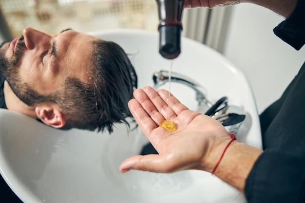 Добрый парикмахер стоит возле раковины и собирается мыть волосы своего клиента