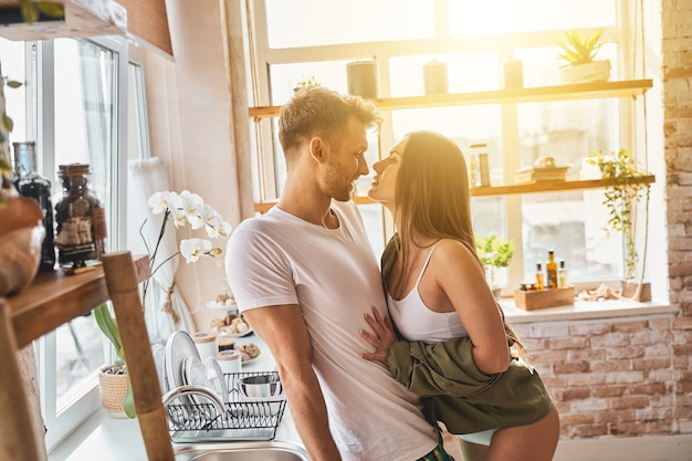 Kind bearded man leaning on furniture while standing close to his girlfriend, spending weekend at home