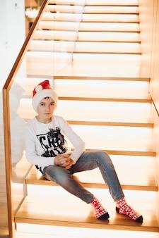 종류 소년 산타 모자를 쓰고 카메라를 똑바로보고. 크리스마스 컨셉