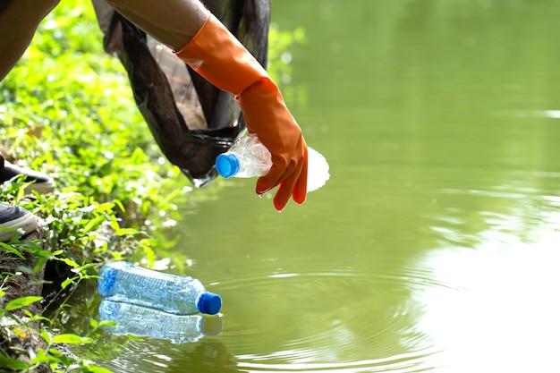 パケットを持って水からペットボトルのゴミを集める親切な環境にやさしいボランティア