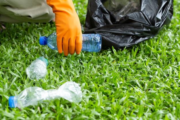 パケットを持ってペットボトルのゴミを集める親切な環境にやさしいボランティア