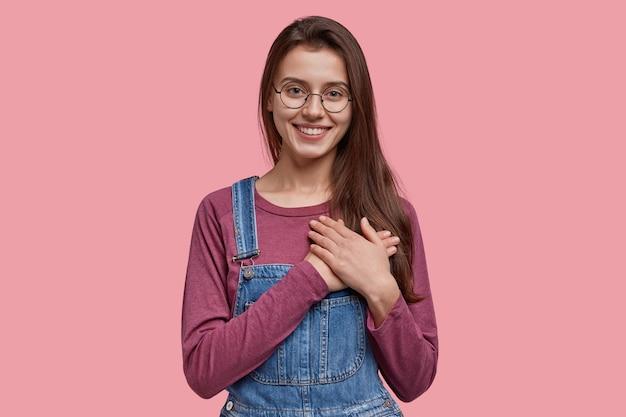 Добрая европейка с приятной улыбкой, выражает любезность, держит обе руки на груди, добрая и честная, одетая в джинсовый комбинезон.