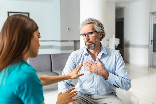 病院で幸せな年配の男性患者を奨励することを受け入れる親切な女性医師。