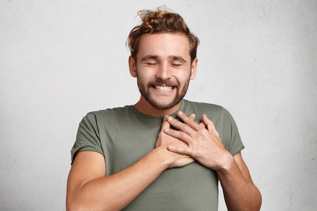 Kind hearted happy hipster guy smiles happily, closes eyes with pleasure, keeps hands on heart,