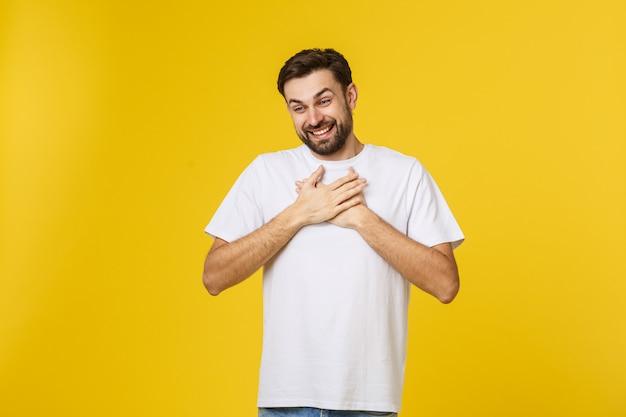 Добросердечный счастливый хипстерский парень счастливо улыбается, закрывает глаза от удовольствия, держит руки на сердце, выражает приятные эмоции, сочувствие и большую любовь