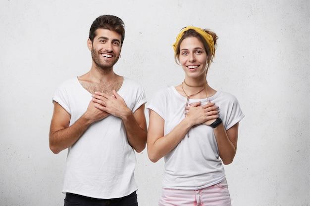 흰색 티셔츠를 입은 상냥한 남녀가 가슴에 손을 모으고 부모가 될 수 있다는 사실에 감사하고 기뻐합니다. 동정심을 보이는 잘 생긴 사람들